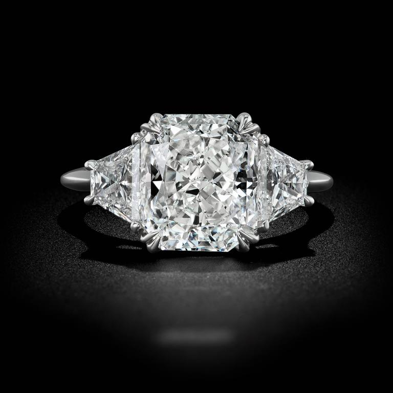 A magnificent take on a traditional design. This impressive three stone engagement ring brings together a fiery collection of bright Diamonds on a band of Platinum. A flawless 4.04 carat Radiant cut Diamond shines seductively between two distinctive
