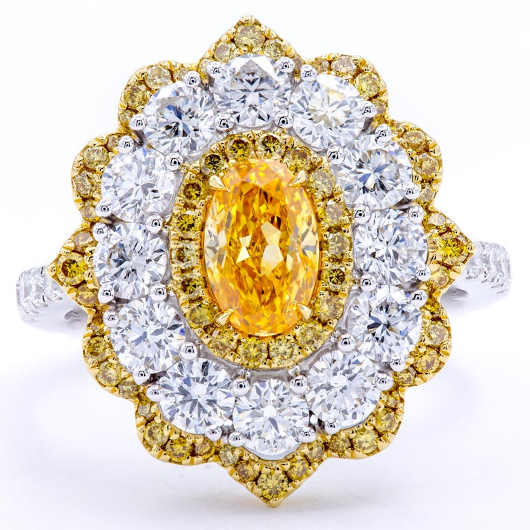 An elegant design exploding with succulent color. This diamond engagement ring shows a bright floral design with petals of natural fancy yellow and white round brilliant diamonds accenting the incredibly colorful GIA certified natural fancy intense