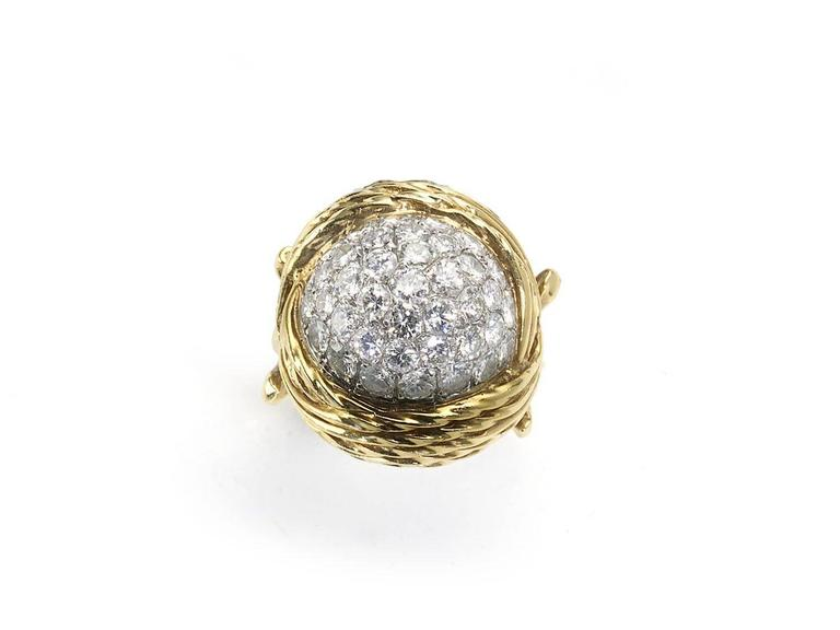 A diamond and gold bombé ring, with a pavé set centre, of round brilliant-cut diamonds, with an estimated total weight of 3.50ct, with a multi-row bark finish surround of twisted wire work, mounted in 18ct gold. Circa 1960s.  Finger size M / USA