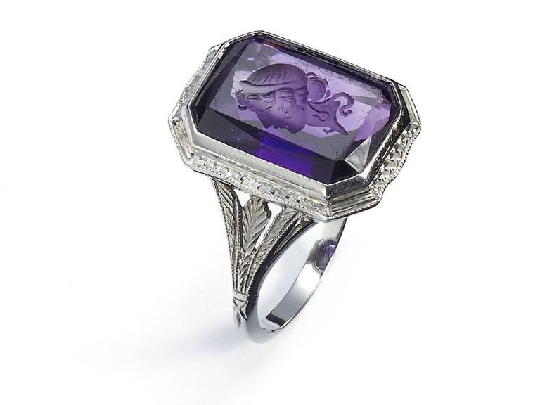 An amethyst intaglio ring, with an emerald-cut amethyst, carved with the head of a Roman style woman, in a millegrain edged rub over setting, with a square nailhead design and millegrain edged surround, with carved and millegrain trefoil shoulders,