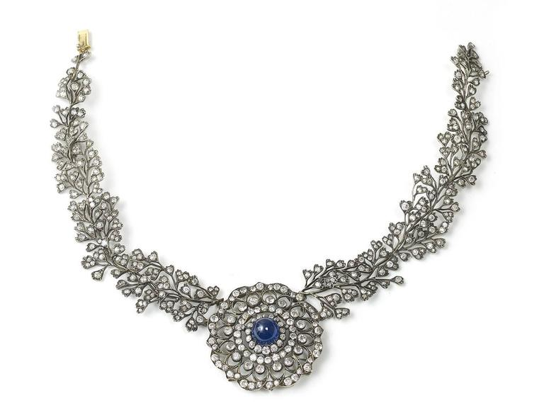 A sapphire and diamond necklace, central circular panel, set with a high cabochon-cut sapphire measuring approximately 12.34 x 12.56mm, within a floral openwork design of old-cut diamonds, integrated collar featuring branches, set with old-cut