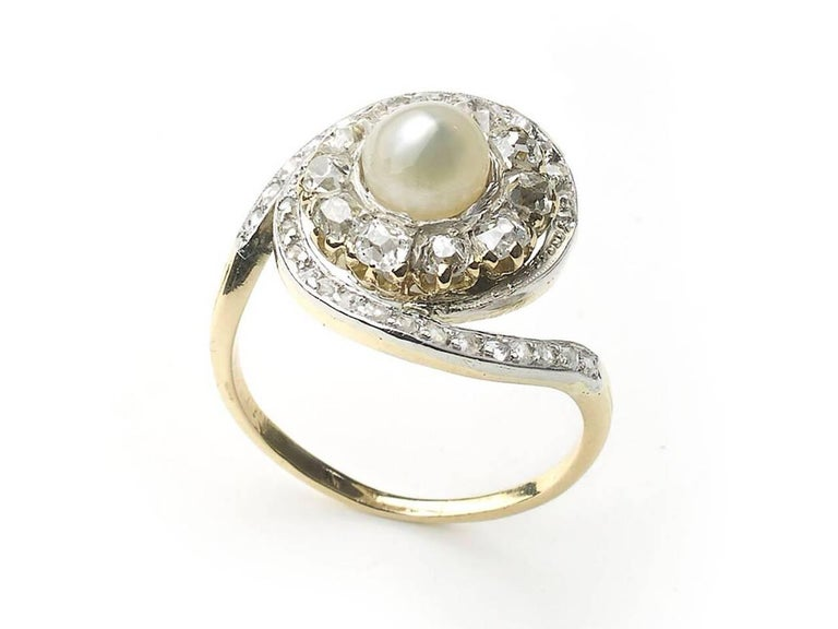 A French, antique, natural pearl ring, with a cluster surround of ten old-cut diamonds, in claw settings, with a swirling surround of rose-cut diamonds, in grain settings, with millegrain edges, set in silver-upon-gold, with a gold shank, with three