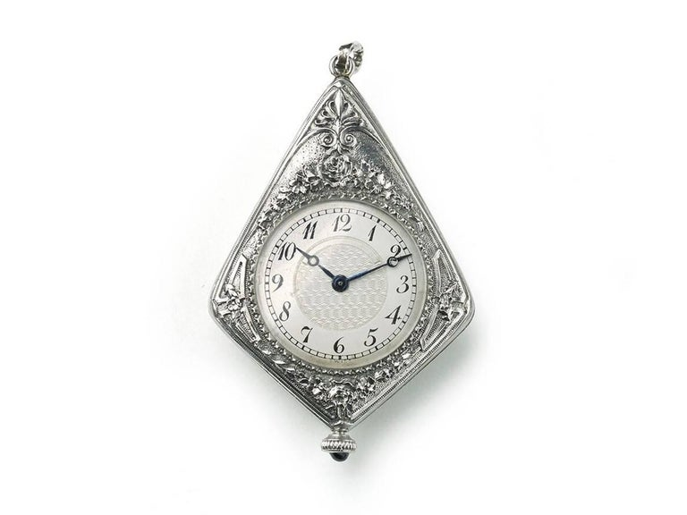 An Art Deco watch pendant, with blue guilloche enamel, with a thistle design within an ace motif, in the centre, set with old-cut and rose-cut diamonds and a foliate engraved and old-cut diamond set surround, on the other side is a watch, with a