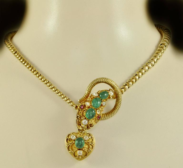 A Victorian 15ct gold snake necklace, set with cabochon emeralds and diamonds, with cabochon ruby eyes.