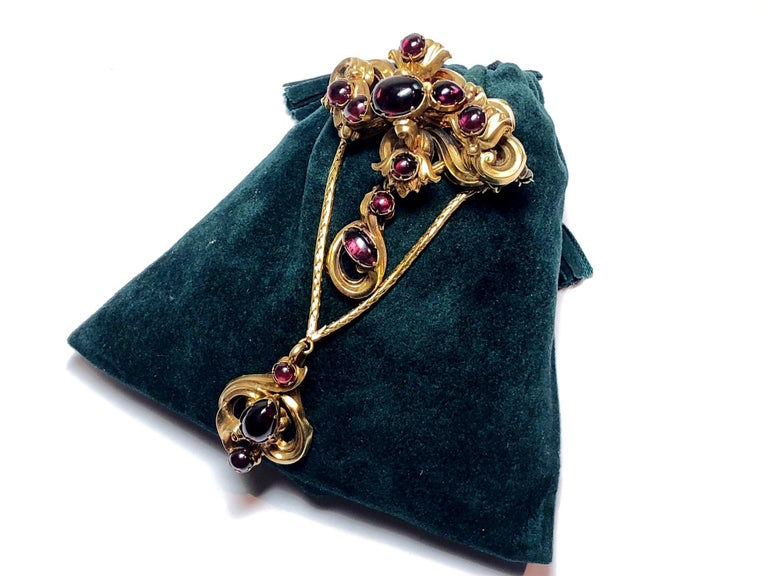 A Victorian garnet brooch, set with cabochon cut garnets set in a floral motif, suspending another cabochon garnet drop, with a further cabochon garnet drop suspended from two gold rope chains, circa 1875