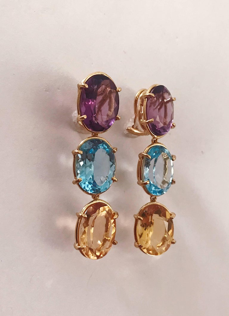 18kt Yellow Gold Elegant Three Stone Drop Earrings with faceted oval Amethyst and Blue Topaz and Citrine.  The Earrings measure 2 1/4 in length. The earrings can be made for Clip Earring or Pierced Earrings. They can also be custom made with any