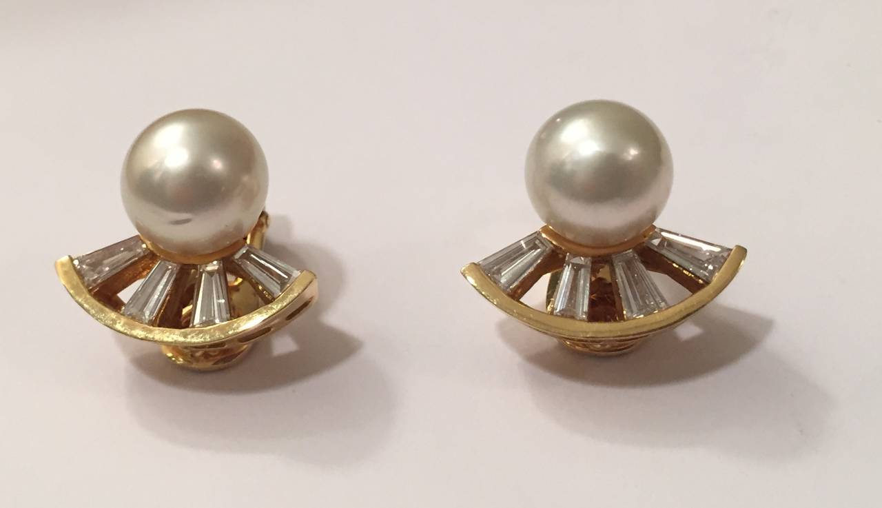 Elegant Pearl and baguette Diamond Ear clips by A. Clunn set in 18kt Yellow Gold.  The pearls measure 12 mm.  The 8 diamond baguettes create a fan like effect.  They weigh approximately 2 carats in total weight.