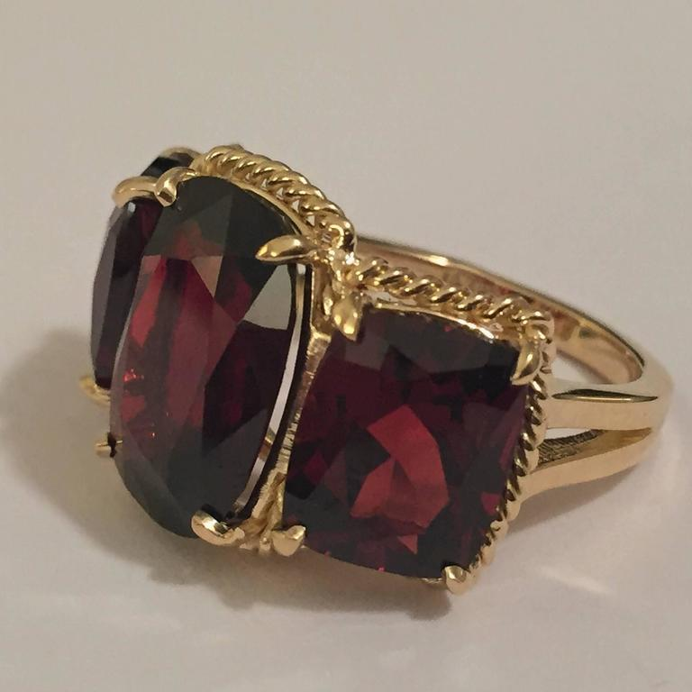 """Elegant 18kt Yellow Three Stone Ring with Rope Twist Border with split shank detail. The ring features three faceted cushion cut Garnet stones surrounded by twisted gold rope. The center Garnet stone measures 5/8"""" tall (including the rope"""