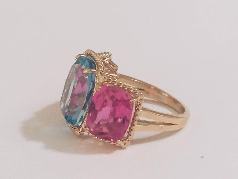 Elegant 18kt Yellow Three Stone Ring with Rope Twist Border with split shank detail. The ring features three faceted cushion cut stones surrounded by twisted gold rope. The center Blue Topaz stone measures 5/8
