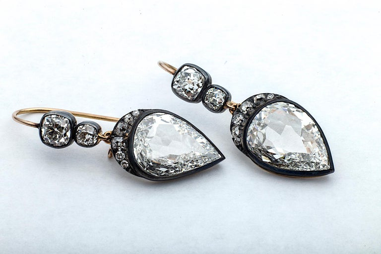 Elegantly subtle yet sensually dazzling, these inverted pear shaped diamonds are crowned with a crescent of old mine cut  diamonds dropping from two cushion cut diamonds.  Framed in antiqued gold and silver mountings, these handmade earrings