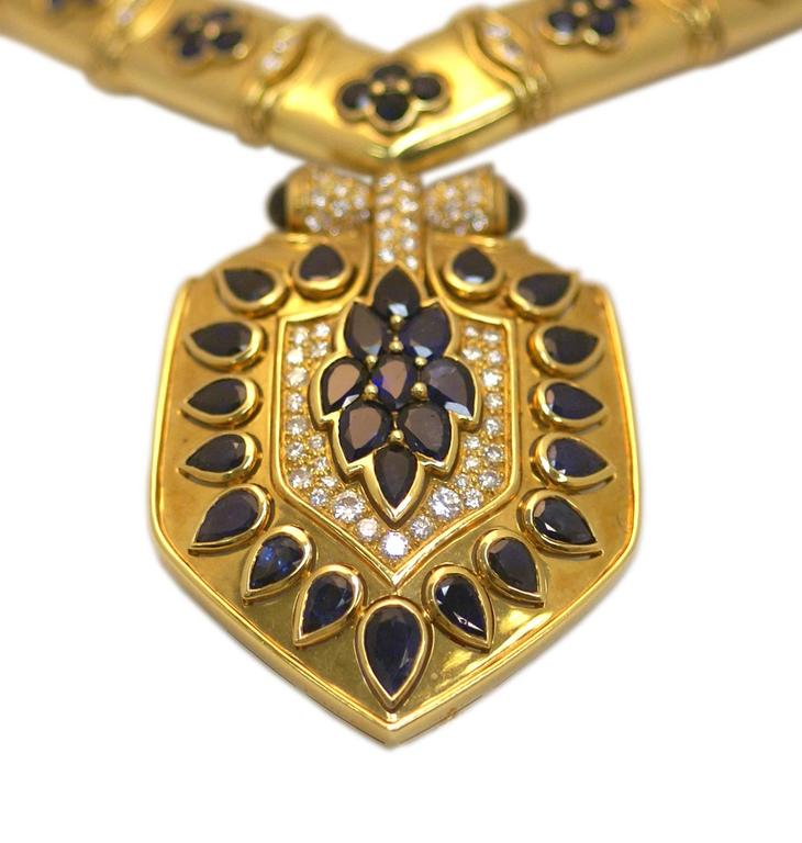 An unusual necklace composed of a V shaped 18kt yellow gold collier, highlighted by round cut sapphires and diamonds, sustaining a large shield (detachable to be worn as a brooch), also embellished with pear shaped sapphires and round cut diamonds.