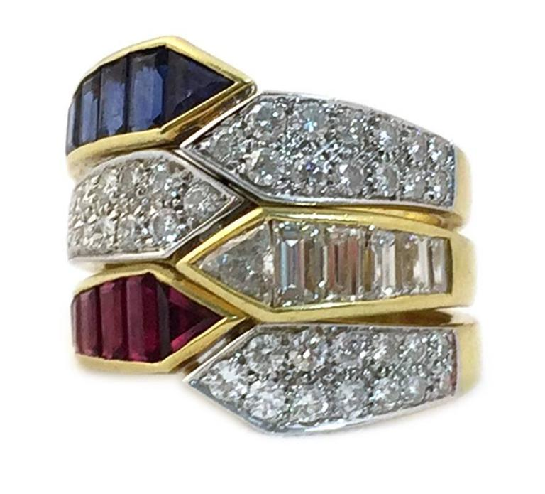 A combination of three rings 18kt gold of identical geometrical design, one with baguette cut and round cut diamonds, one with baguette cut rubies and round diamonds, and the third with baguette cut sapphires and round cut diamonds. Wearable all