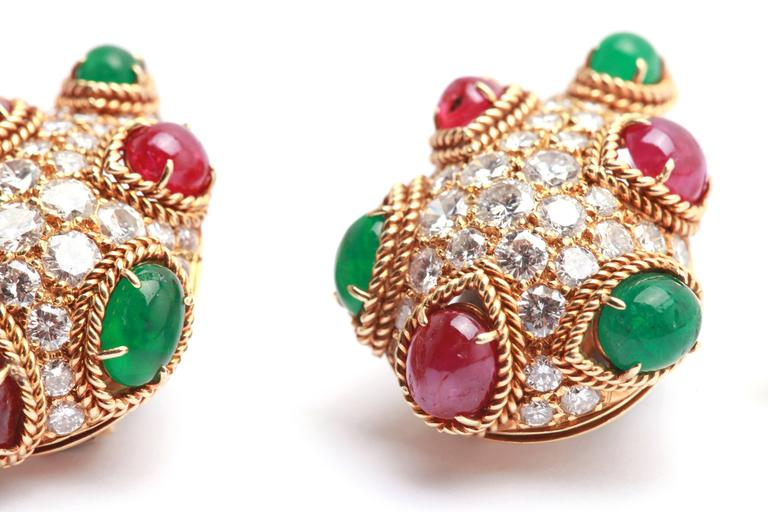 A sophisticated and colorful pair of pear shaped ear clips by Van Cleef & Arpels, with fine brilliant diamonds, embellished by cabochon rubies and emeralds. Made in France, circa 1965.