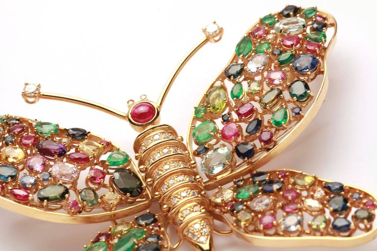 An impressive and large 18kt yellow gold brooch resembling a Butterfly, encrusted with multicolor sapphires, rubies and emeralds. Circa 1980s