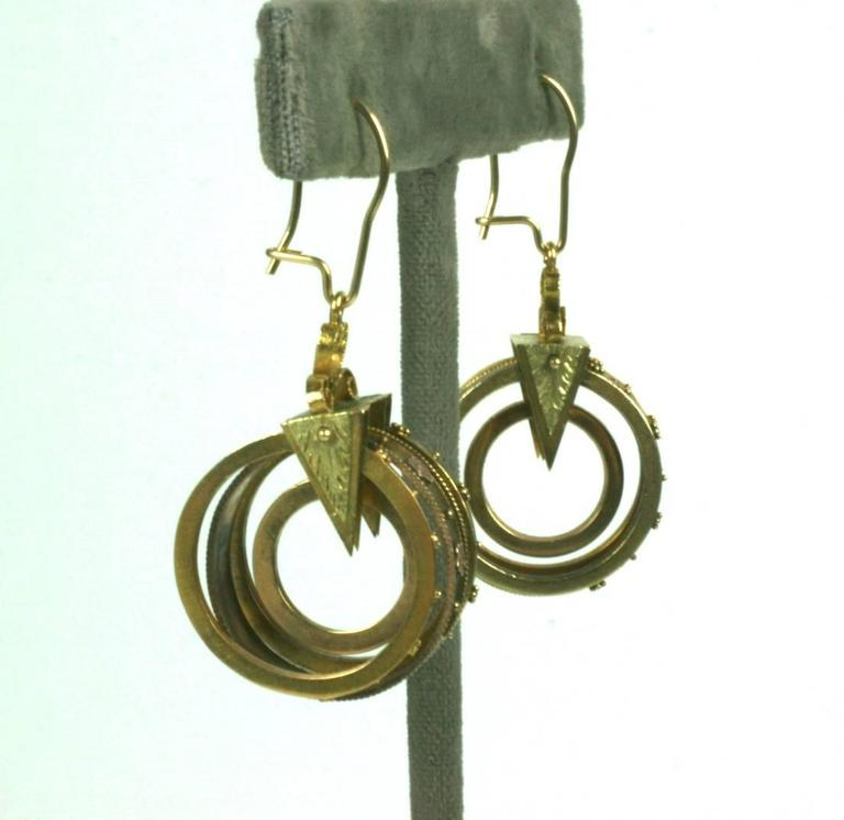Extremely unusual Victorian Earrings in the Archeological Revival style, constructed of a series of gold hoops in varicolored gold (green and pink), decorated with tiny shot work and flower heads. These are held in place by an engraved triangular