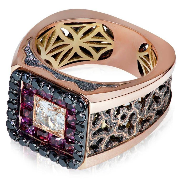 """Alex Soldier """"Infinite Greatness"""" Men's Ring in 18 karat rose and yellow gold with diamonds and rhodolite garnets. Center white diamond: 0.75 ct. Small white diamonds: 4 stones, total carat weight: 0.02 ct. Black diamonds: 28 stones, total"""