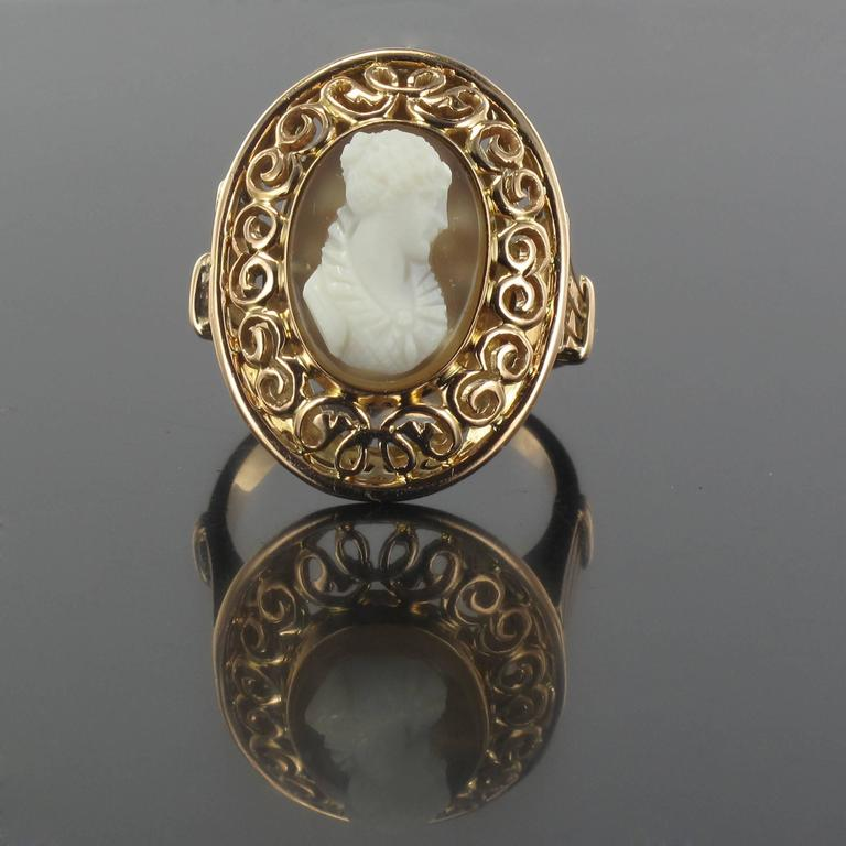 Ring in 18 carat rose gold, eagle head hallmark.  This voluminous oval shaped antique ring is set with a cameo on agate depicting the profile of a young woman with her hair up. The ring bed is engraved with arabesques on the face and sides.  Height: