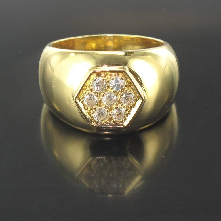 Ring in 18 carat yellow gold.  This large domed band ring is set with a hexagonal shaped design featuring 7 claw set brilliant cut diamonds.   Total diamond weight: about 0.30 carat. Height: 1.14 cm, ring width in base: 2.15 mm. Total weight:
