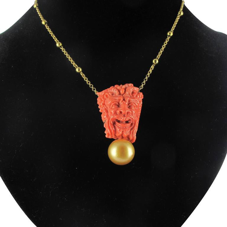 Baume creation - unique piece. Necklace in 18 carat yellow gold. This splendid and original yellow gold necklace is composed of a double belcher chain interspersed by golden beads. This gold beaded chain holds a coral cameo with a smirking Bacchus