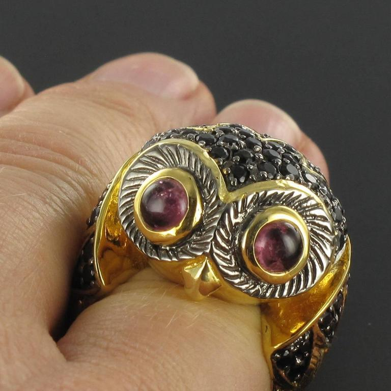 Silver ring.  This highly original animal themed ring features the head of an owl. Its bewitching eyes are tourmaline cabochons and its feathers are black spinals set in gold plated silver. This ring is a good size whilst being comfortable to wear