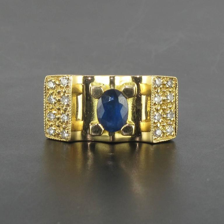 Ring in 18 carat yellow gold, eagle head hallmark.   This sapphire ring is reminiscent of the tank rings of the 1940s. In the form of a bridge the central faceted oval blue sapphire is held by 4 large claws and set at each side with 8 brilliant