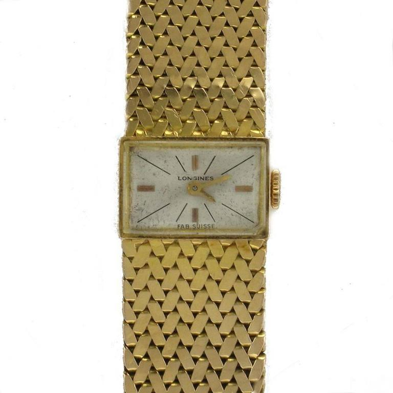 Longines Women's watch Bracelet and Rectangular case in 18 carats yellow gold, eagle head hallmark. Revised and controlled watch - Very good condition and general appearance. Mechanical watch with manual winding. Cream background. Vintage watch