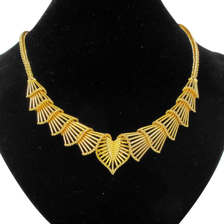 18 carat yellow gold necklace, 750 thousandths, rhinoceros head hallmark.   This superb gold necklace features a design formed of curved openwork gold fan shapes edged with gold braid. This series of motifs is connected at each end to a palm link