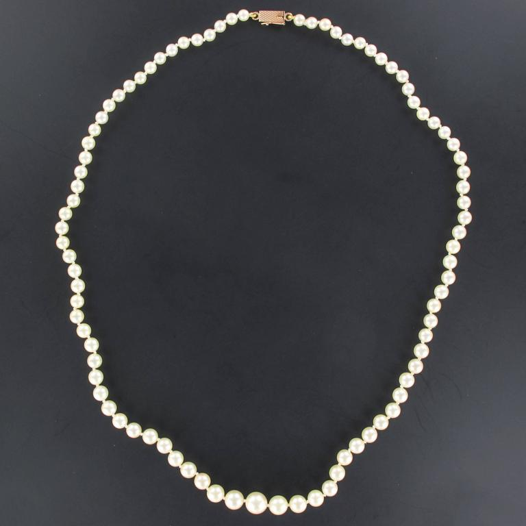 This pearl necklace is composed of a strand of Japanese cultured pearls which are held together by an 18 carats rectangular rose gold clasp.   Diameter of the pearls: 5,5/6 mm. Overall length: 55,5 cm. Total weight: approximately 21,1 g.  The
