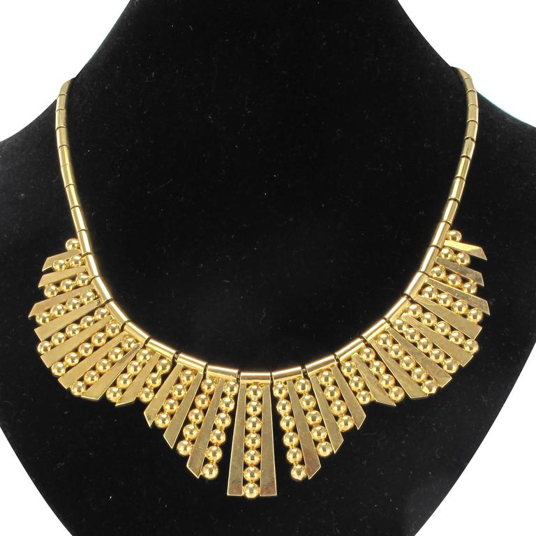 18 carat yellow gold necklace, 750 thousandths.  This splendid antique necklace is composed of a gold Rolo link chain threaded with gold cylinders and a curved design formed of flat gold plates alternating with columns of round gold beads. This