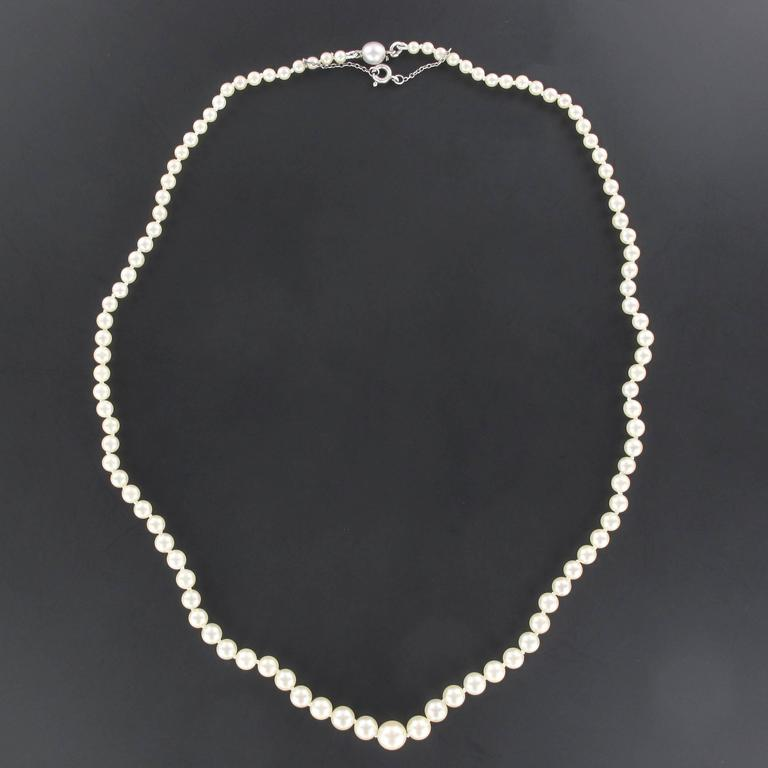 This pearl necklace is composed of a strand of Japanese cultured pearls which are held together by an 18K wight gold clasp is concealed in an oval pearl at the tip.  Diameter of the pearls: 3/3,5 to 7/7,5 mm. Overall length: 49,5 cm. Total weight: