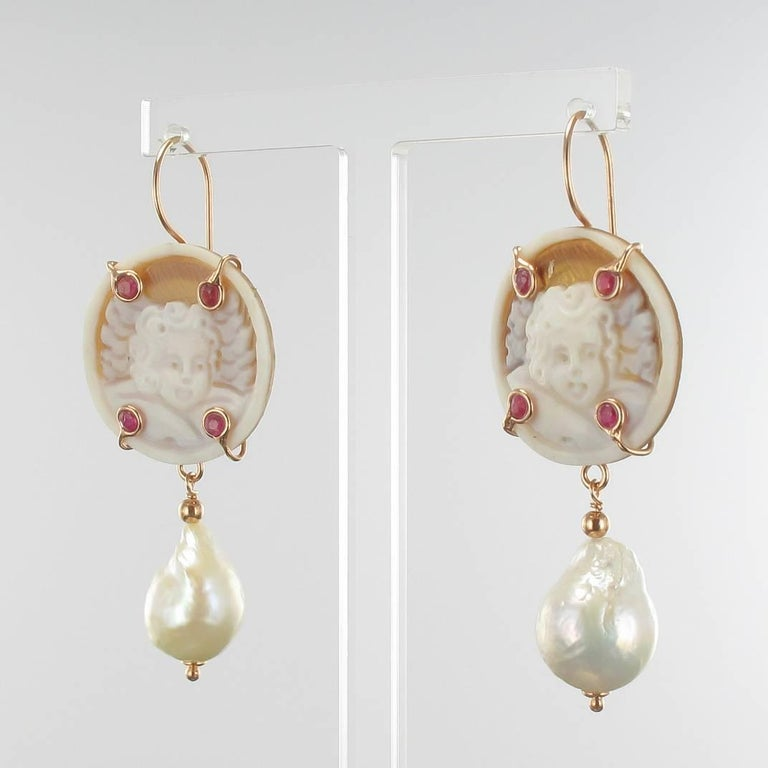 For pierced ears.  Pair of earrings in vermeil, silver and rose gold.  Earrings are set with a cameo on shell representing an angelot set with 4 red crystals and which retains in pampille a baroque cultured pearl . The clasp is a gooseneck with