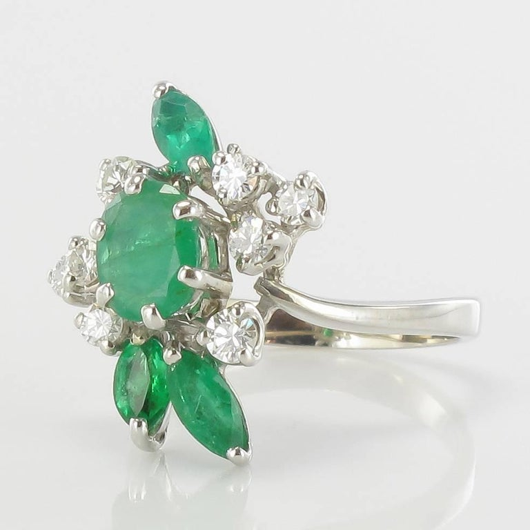 Ring in 18 carats white gold, head of eagle hallmark.  It comes straight from the 1970s, this splendid vintage ring is set with claws of an emerald oval surrounded by 8 modern brilliant cut diamonds and 3 emeralds shuttle.  Total diamond weight:
