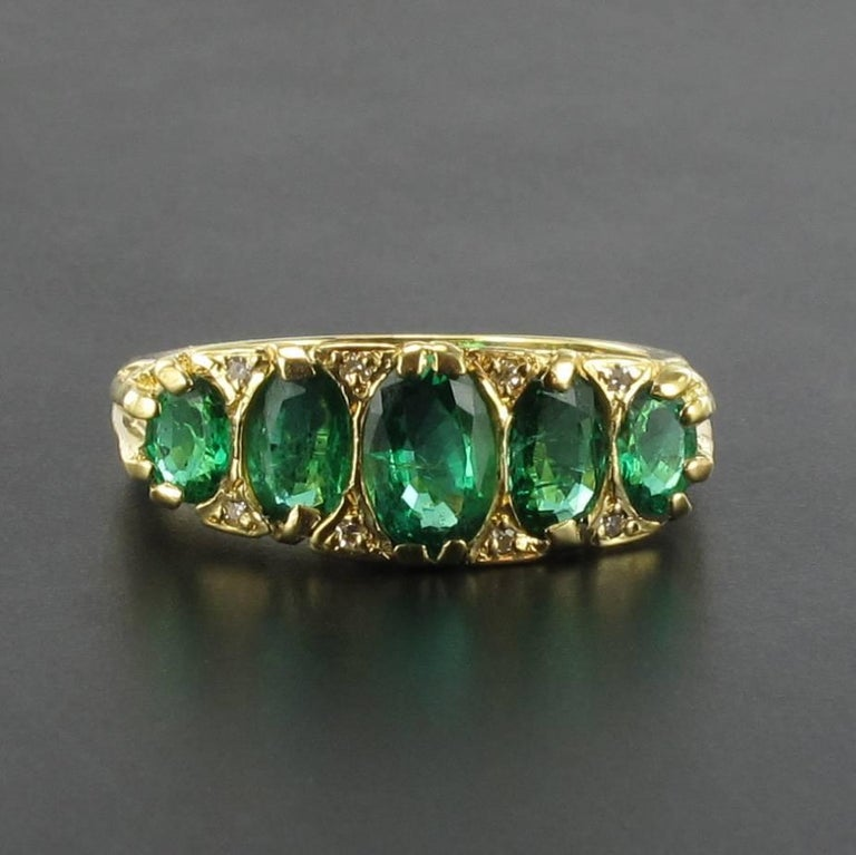 """18 carats yellow gold ring, english hallmarks.  Called """"jarretière"""" ring, it is set on its top of 5 emeralds oval faceted and rose cut diamonds between each of them.   Total weight of emeralds: 1.66 carat approximately. Height at the highest: 7.8"""