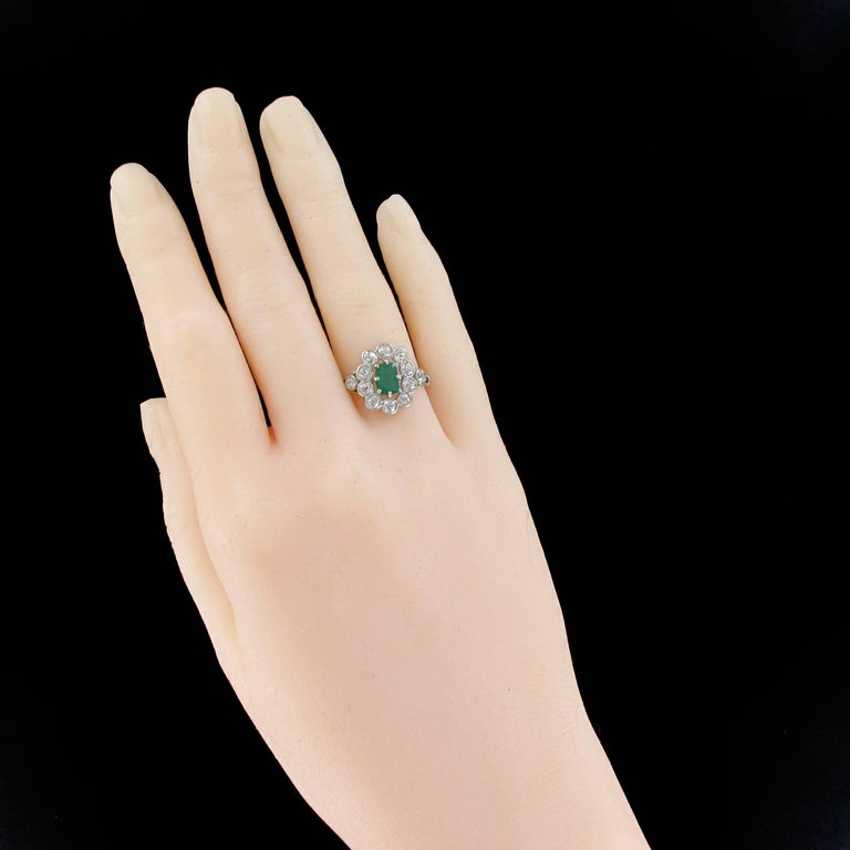Ring in 18 carats white gold.   Absolutely splendid, this antique ring is set with 8 claws on its top of an intense green emerald surrounded by 10 antique brilliant cut diamonds in millegrains set. On either side, another diamond is set on the start