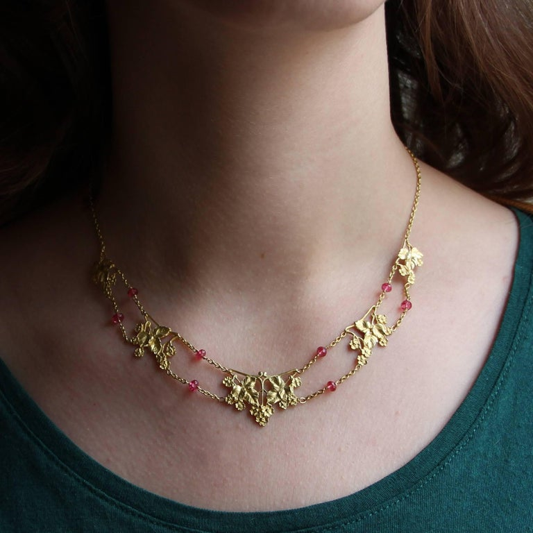 18 caarts yellow gold necklace, eagle's head hallmark. Lovely gold drapery, it is made of carved ivy leaf motifs and retained between them by a double chain punctuated with faceted pink spinel beads. The clasp is a spring ring. Total length: 42 cm,