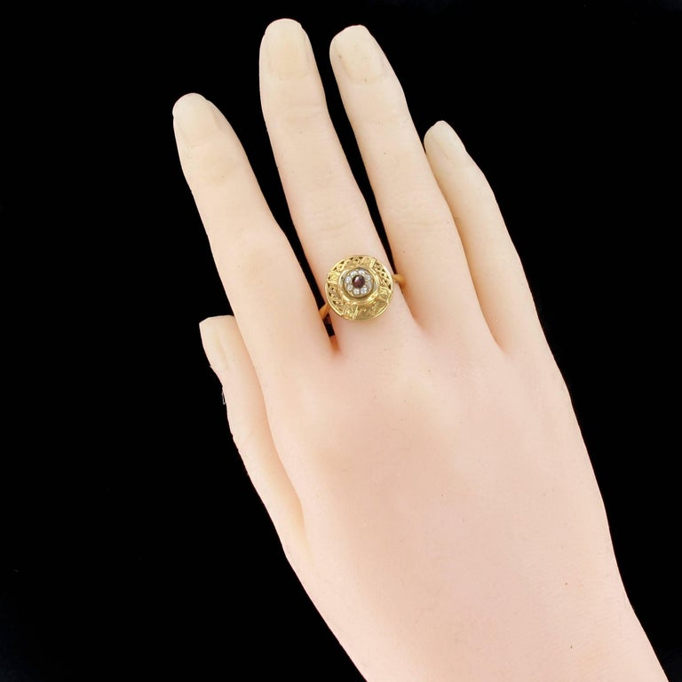 A set consisting of a bracelet, a brooch and a ring in 18K Yellow Gold, eagle head hallmark. It is decorated on top with a round pattern, an engraved geometric design, bordered with a golden double twist highlighted with garnets and fine pearls. The