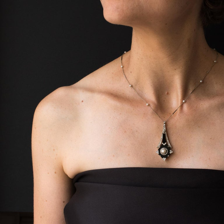 Platinum pendant, dog's head hallmark.  Composed of a geometric pattern in polished onyx with a large fine pearl in the centre surrounded by rose cut diamonds with diamond set clips in the corners. On the upper part, a line of diamonds is set in