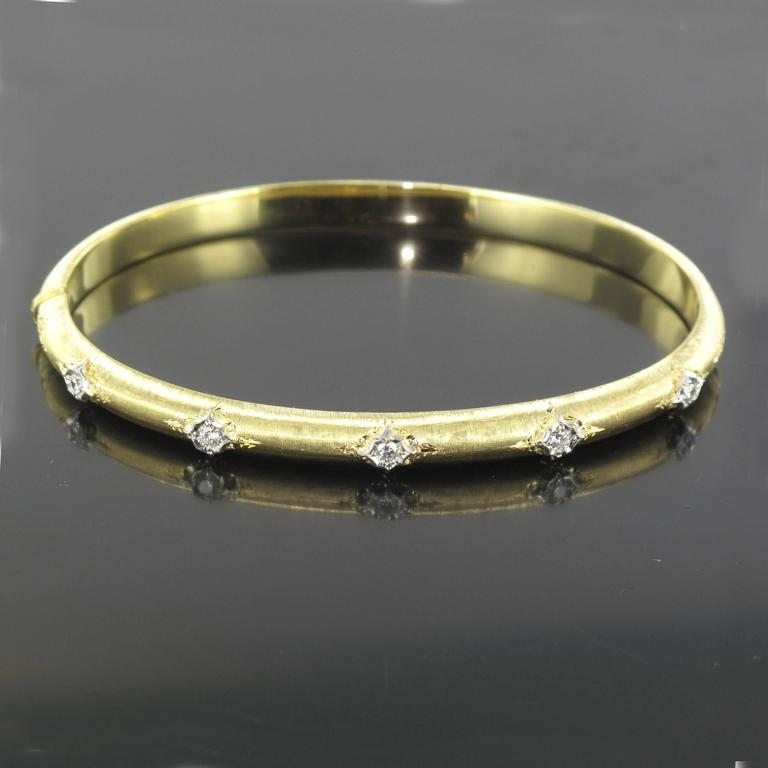 Bangle bracelet in 18 carat satin yellow gold. This lovely oval and rounded bracelet is made from brushed yellow gold that is engraved and set with 5 brilliant cut diamonds. This diamond bracelet opens with a hinge.  Total diamond weight: about 0.20