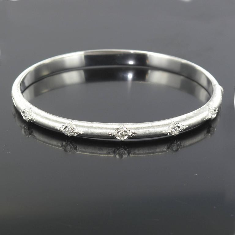 Bangle bracelet in 18 carat satin white gold. This delightful white gold bangle bracelet is oval and rounded in form. Created in brushed white gold it is engraved and set with 5 brilliant cut diamonds at the front, it opens with a hinge.  Total