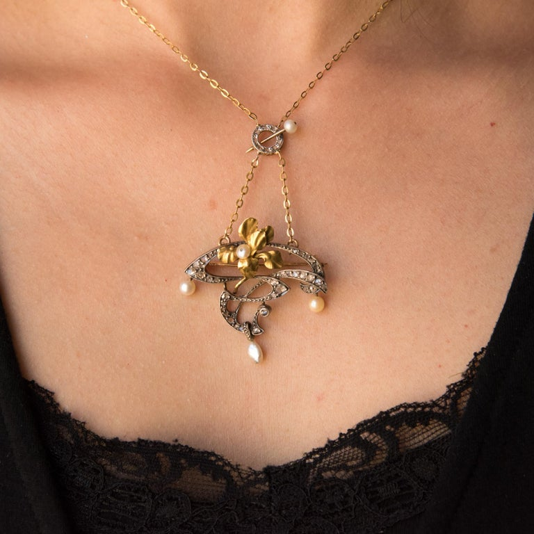 18 carat yellow gold and silver necklace eagle's head hallmark.  Featuring an openwork floral design set with rose cut diamonds. The necklace features a yellow gold Iris motif set with a fine flat pearl. Suspended from the pendant are 3 white beige