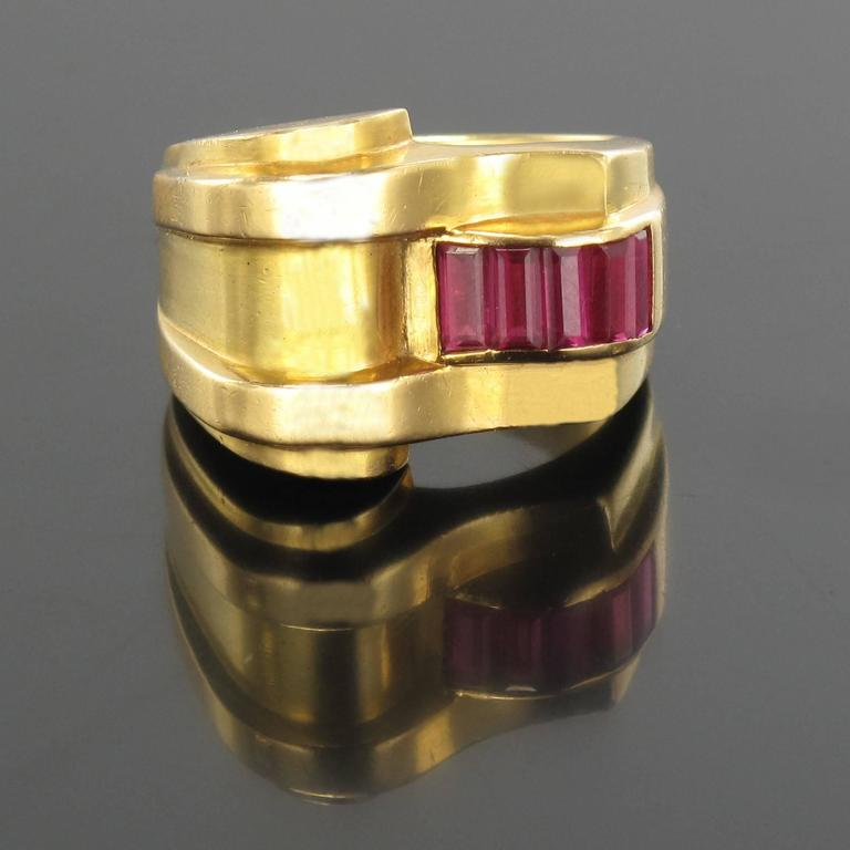 Ring in 18 carat yellow gold, eagle head hallmark.  A voluminous and asymmetrical ring that features 5 synthetic calibrated rubies in invisible settings.  Width: 1.7 cm, height at the top: 0.7 cm, ring width at the base: 6.5 mm. Total weight of the
