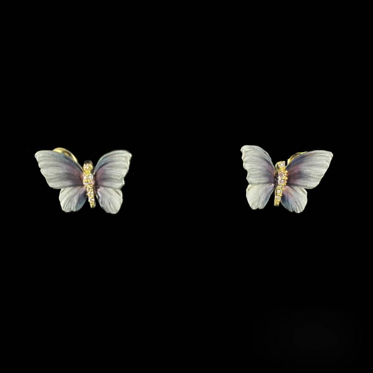 For pierced ears.  Earrings in 18 carat yellow gold.   These earrings are in the form of butterflies in flight, the wings are beautifully reproduced in shades of glittering blue enamel. The bodies are covered in diamonds. The clasps are butterfly