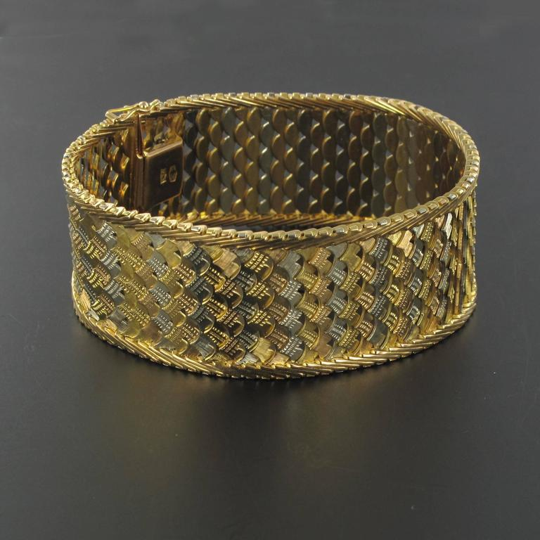 Bracelet in 18 carat yellow gold and white gold.  This magnificent bracelet is composed of openwork chiselled and woven white and yellow gold edged with golden ears of wheat. This flexible bracelet from the 1960s rests comfortably on the wrist and