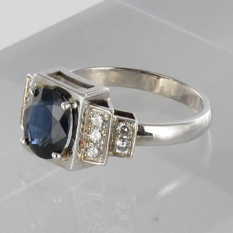 Baume Creation - Unique piece    18 carat white gold ring, eagle head hallmark.    This sublime ring was inspired by the clean cut modern lines of the Art Deco movement. It is composed of a square design set with an intense blue oval cut