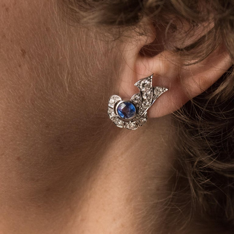 For pierced ears. Pair of platinum earrings, dog head hallmark and 18 carat white gold, eagle head hallmark.  In the form of bows, these Art Deco earrings are bezel set with round sapphires in openwork settings with antique brilliant cut diamonds.
