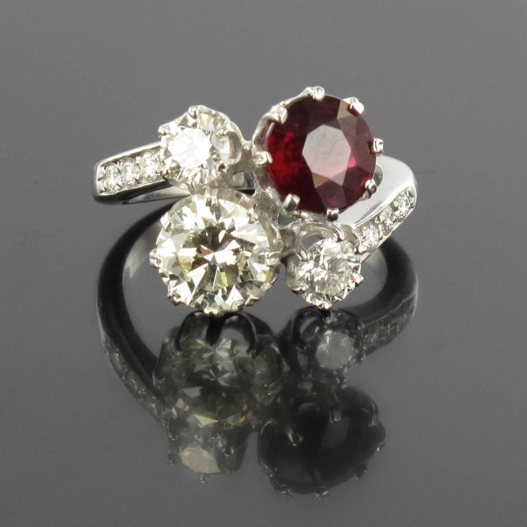 Ring in 18 carat white gold, eagle head hallmark.  Featuring a claw set round ruby and a brilliant cut diamond, another smaller diamond is set at each side with a further 3 small diamonds leading into the ring band on each side.  Ruby Weight : 2.04
