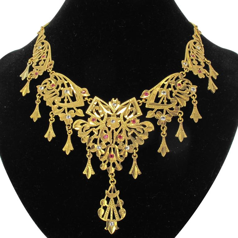 18 carat yellow gold necklace.  An imposing antique necklace formed of 5 finely engraved articulated gold plates with arabesque openwork and leafy motifs. The design is set with small white sapphires and red gems. The necklace is completed with