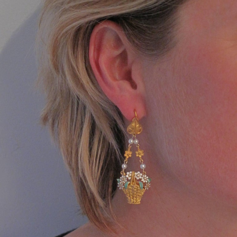 For pierced ears. Earring in matte vermeil. These beautiful vermeil earrings are made of a leaf that supports in pendants a basket of enamelled flowers and crimped with small crystals. It is held by 2 chains consisting of flower motifs and small