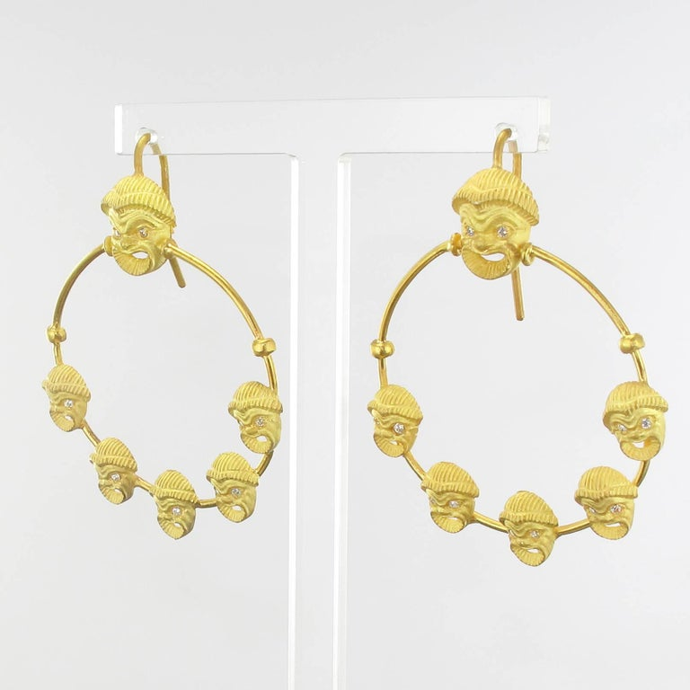 For pierced ears. Earring in matte vermeil. These splendid vermeil earrings are made of a delicately chiseled grinning mask whose eyes are set with small crystals. It retains a large gold ring set with applied same motif in mask. The hanging system