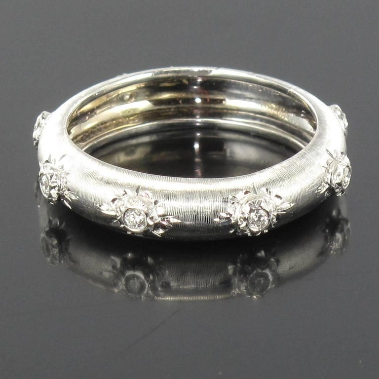 Ring in 18 carat white gold. Superb rounded brushed white gold ring, engraved and set with 7 brilliant cut diamonds. This ring would admirably fit the role as an exquisite eternity ring.  Total diamond weight: about 0.10 carat. Width: 4.6 mm. Total